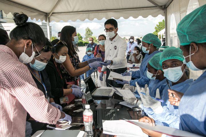 Le président malgache (au centre avec masque et lunettes de vue) dans un centre de tests de dépistage du Covid-19 à Antananarivo le 31 mars 2020. (RIJASOLO / AFP)