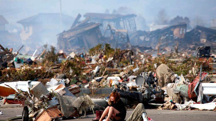 Une femme pleure, assise sur une route, après qu'un tremblement de terre suivi d'un tsunami a ravagé la ville de Natori, au nord du Japon, le 13 mars 2011. Ce phénomène naturel a également déclenché l'accident nucléaire de Fukushima, plus grave catastrophe nucléaire du 21e siècle. (ASAHI SHIMBUN / REUTERS)