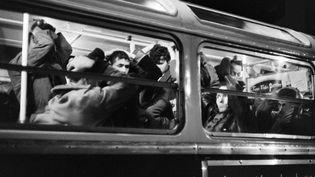 Des manifestants algériens les mains sur la tête dans un bus de la RATP réquisitionné par la police, le 17 octobre 1961. (AFP)