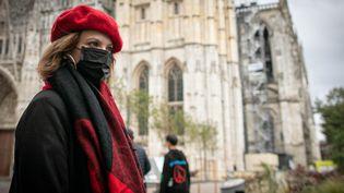Une femme portant un masque de protection devant la cathédrale de Rouen (Seine-Maritime), le 26 septembre 2019, quelques heures après l'incendie d'un site classé Seveso du sud de la ville. (LOU BENOIST / AFP)