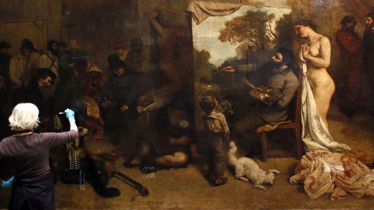 """Le tableau de Courbet """"L'Atelier du peintre"""", pendant la restauration (déc 2014)  (PATRICK KOVARIK / AFP)"""