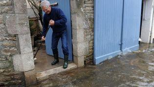Un habitant de Quimperlé (Finistère) tente de nettoyer l'entrée de son domicile après les crues, vendredi 3 janvier 2014. (FRED TANNEAU / AFP)