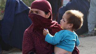 Une Afghane et son enfant dans un camp de Kaboul, le 11 août. (HAROON SABAWOON / ANADOLU AGENCY/AFP)