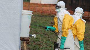 Des travailleurs d'un centre de traitement des malades d'Ebola à Lokolia, en République Démocratique du Congo, le 5 octobre 2014. (KATHY KATAYI / AFP)