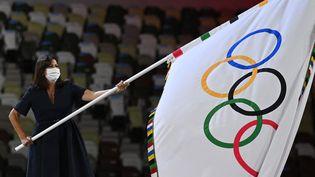La maire de Paris Anne Hidalgo brandit le drapeau olympique lors de la cérémonie de clôture des Jeux olympiques de Tokyo au sein dustade national japonais,le 8 août 2021, symbolisant la passation entre Tokyo et Paris. La capitale française accueillera les prochains Jeux olympiques d'été du 26 juillet au 11 août 2024, cent ans après les derniers Jeux de Paris, et 32 ans après les Jeux olympiques d'hiver d'Albertville. (DANIEL LEAL-OLIVAS / AFP)