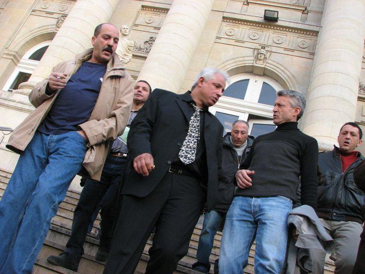 Nouredine Gaham (au centre de la photo, avec la cravate), au sortir du tribunal d'Amiens, le 18 février 2008. (MAXPPP)