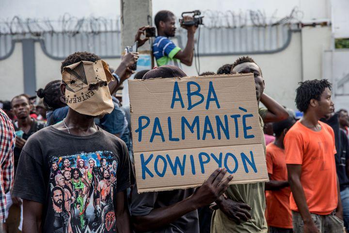 """Des manifestants portent une pancarte indiquant """"A bas les législateurs corrompus"""", lors d'un rassemblement à Port-au-Prince, le 18 novembre 2019. (VALERIE BAERISWYL / AFP)"""
