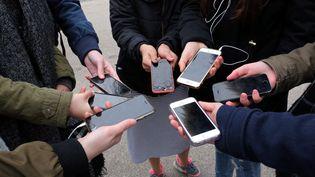 Un groupe d'adolescents avec leur téléphone portable, à Thonville (Moselle), le 8 février 2017. (MAXPPP)