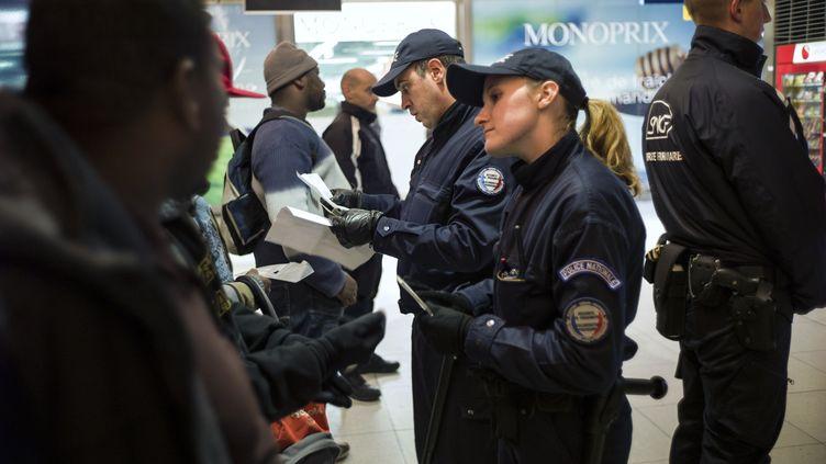 Des policiers contrôlent l'identité d'un groupe d'individus à la garde du Nord à Paris, le 30 novembre 2012. (FRED DUFOUR / AFP)