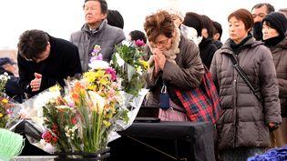 Ici en mars 2016 à Sendai (Japon), des personnes prient pour les victimes du tremblement de terre et du tsunami qui ont frappé le Japon en 2011 (TORU YAMANAKA / AFP)