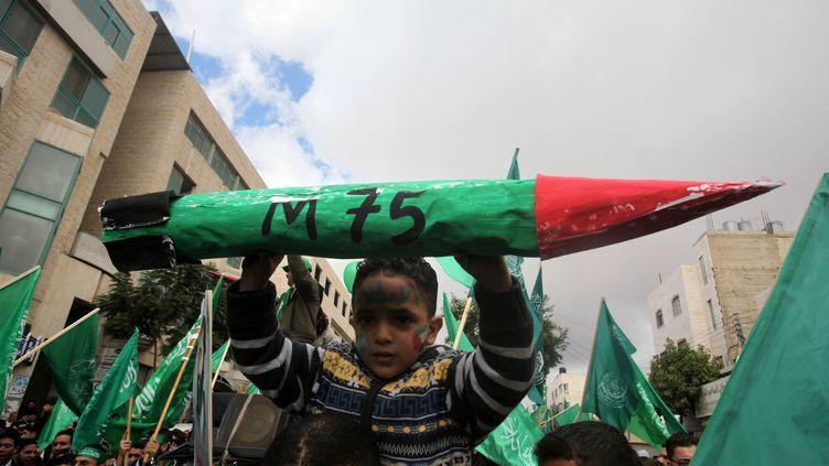 Un enfant palestinien porte l'effigie d'une roquette artisanale de type M75, lors du 25e anniversaire de la création du Hamas, le 14 décembre 2012 à Hébron (Cisjordanie). (HAZEM BADER / AFP)