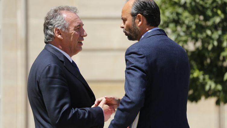 Le ministre de la Justice François Bayrou serrant la main du Premier ministre, Edouard Philippe, le 14 juin 2017, dans la cour de l'Elysée à Paris, après le Conseil des ministres. (PATRICK KOVARIK / AFP)