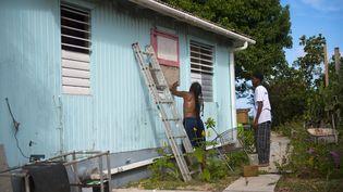 Des habitants de Saint-Martin installent des panneaux de bois pour protéger leur maison avant le passage de l'ouragan Irma, mardi 5 septembre 2017. (LIONEL CHAMOISEAU / AFP)