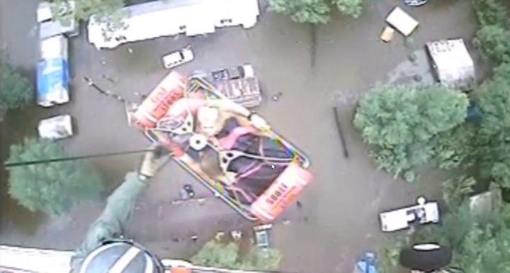 Un secouriste évacue trois habitants depuis le toit d'une maison inondée de Baton Rouge, dans l'Etat américain de Lousiane, samedi 13août 2016. (US COAST GUARD / REUTERS)