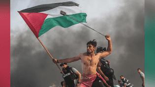 Un Palestinien lance des pierres lors des manifestations contre le blocus de Gaza, le 22 octobre 2018. (MUSTAFA HASSOUNA / ANADOLU AGENCY / AFP)