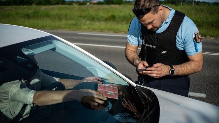 Un gendarme contrôle un automobiliste, le 7 mai 2020, sur une route de Bourg-en-Bresse (Ain). (NICOLAS LIPONNE / HANS LUCAS)