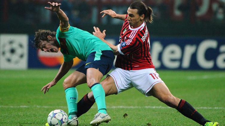 Zlatan Ibrahimovic à la lutte avec Carlos Puyol.  (OLIVIER MORIN / AFP)