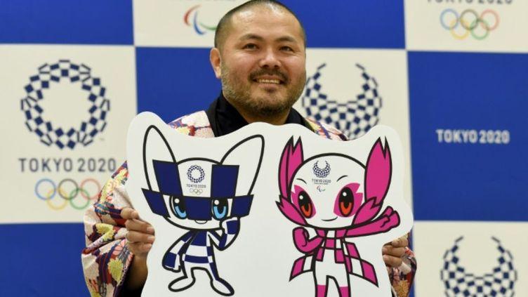 Ryo Taniguchi pose avec les deux mascottes de Tokyo-2020 qu'il a créées