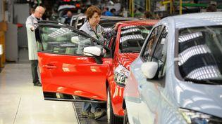 Des employés de Renault surveillent la chaîne de production lors d'une visite du ministre Arnaud Montebourg, le 28 mai 2013, dans l'usine deFlins (Yvelines). (WITT / SIPA)