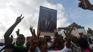 Les partisans de Laurent Gbagbo le 31 août 2020, lors du dépôt de sa candidature à la présidentielle d'octobre, brandissent une photo de l'ancien président ivoirien. (SIA KAMBOU / AFP)