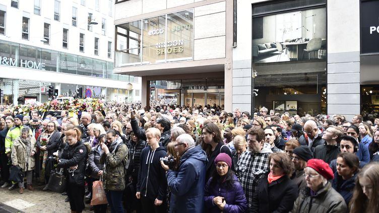 Une minute de silence sur les lieux où une attaque au camion bélier a fait quatre morts, dans le centre de Stockholm (Suède), lundi 10 avril 2017. (NOELLA JOHANSSON / TT NEWS AGENCY / AFP)