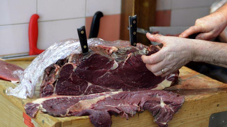 Un artisan boucher découpe un morceau de viande de cheval, à Marseille, le 21 février 2013. (GERARD JULIEN / AFP)
