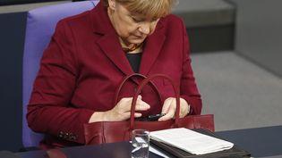Angela Merkel consulte son téléphone au Bundestag, l'Assemblée allemande, à Berlin, le 15 octobre 2015. (HANNIBAL HANSCHKE)