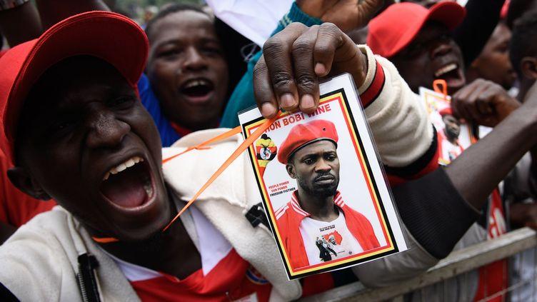 Une foule déchaînée attendait la pop star sur les rives du lac Victoria. De retour sur scène pour la première fois depuis son emprisonnement en août 2018 pour trahison, après des jets de projectiles sur le convoi présidentiel dans le nord de l'Ouganda, «le président du ghetto»a interprété des titres dénonçant la corruption et la pauvreté. Il a aussi confirmé à mots couverts sa candidature à la présidentielle de 2021. (ISAAC KASAMANI / AFP)