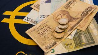 Des drachmes, l'ancienne monnaie grecque, et des euros. (DENIS CHARLET / AFP)