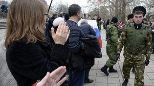 Des personnes applaudissent des volontaires pro-russes chargés de protéger le Parlement de Crimée, pendant une manifestation pro-russes à Simferopol, jeudi 6 mars 2014. (ALEXANDER NEMENOV / AFP)