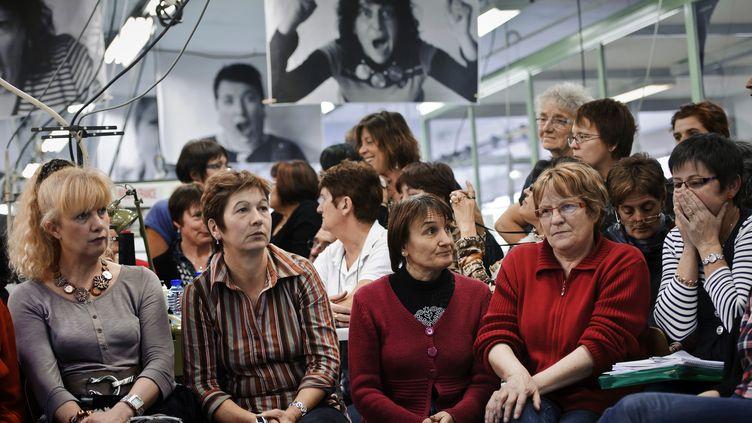 Des ouvrières de l'usine Lejaby à Yssingeaux (Haute-Loire) écoutent l'annonce de reprise de leur entreprise par une filiale de Louis Vuitton, le 1er février 2012. (JEAN-PHILIPPE KSIAZEK / AFP)