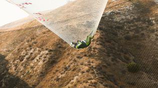 Le parachutiste et cascadeur Luke Aikins rattrapé par un filet de sécurité après un saut de plus de 7 600 mètres sans parachute, le 30 juillet 2016 en Californie. (MARK DAVIS / AFP)