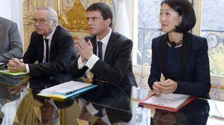 Le Premier ministre, Manuel Valls, entouré de la ministre de la Culture, Fleur Pellerin, et du ministre du Travail, François Rebsamen, le 7 janvier 2015, à Matignon, à Paris. (BERTRAND GUAY / AFP)