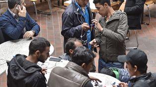 Des migrants utilisent leur téléphone, le 6 septembre 2015 à Dortmund (Allemagne). (MARTIN MEISSNER / AP / SIPA)