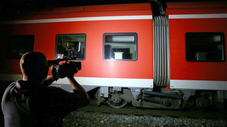 Un caméraman filme le train dans lequel un adolescent afghan a agressé des passagers à la hache, le 18 juillet 2016 à Wurtzbourg, en Allemagne. (KARL-JOSEF HILDENBRAND / AFP)
