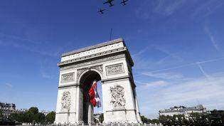 Des avions militaires survolent l'Arc de triomphe à Paris pour le défilé du 14-Juillet en 2017. (ETIENNE LAURENT / AFP)