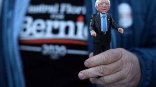 Un supporter de Bernie Sanders tient une figurine du candidat démocrate lors d'un meeting àDes Moines, dans l'Iowa, le 2 février 2020. (ALEX WONG / GETTY IMAGES NORTH AMERICA)