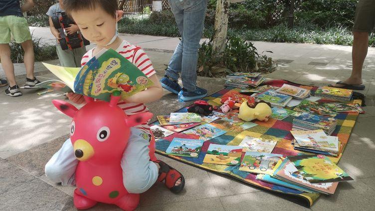 Un enfant joue près d'un marché aux jouets, à Chengdu, en Chine, le 6 juin 2020. (XIAO YI / AFP)