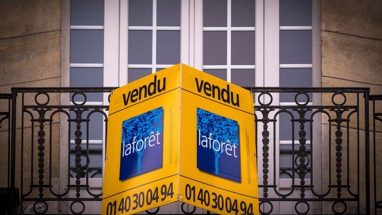 Un panneau d'agence immobilière à la fenêtre d'un appartement vendu à Paris, le 19 décembre 2017. (illustration) (LIONEL BONAVENTURE / AFP)