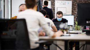Des salariés dans une entreprise qui portent des masques. (THOMAS PADILLA / MAXPPP)