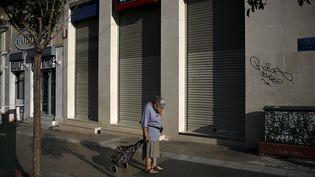 Une femme devant une banque fermée à Athènes (Grèce), le 29 juin 2015. (ALKIS KONSTANTINIDIS / REUTERS)