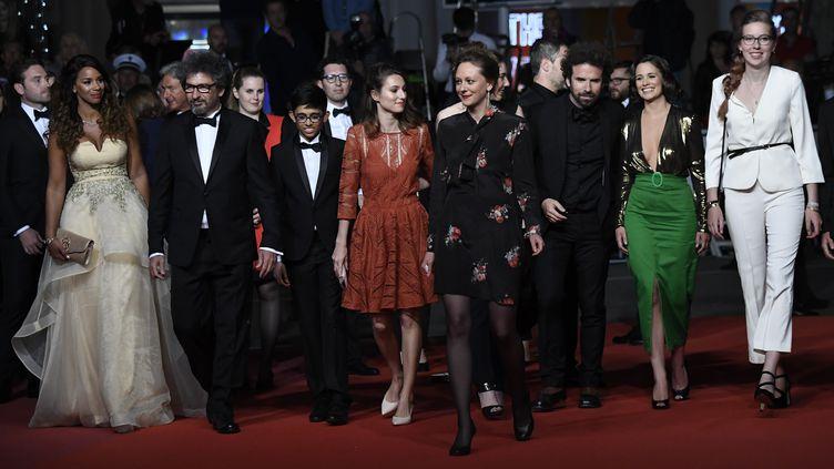 Radu Mihaileanu,Cyril Dion etLucie Lucas, lors de la montée des marches au Festival de Cannes avant la projection de Sorry we missed you, le 16 mai 2019. (CHRISTOPHE SIMON / AFP)