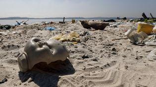 Une tête de poupée retrouvée sur une plage de la baie de Guanabara, près de Rio (Brésil), le 30 juillet. (SERGIO MORAES / REUTERS )