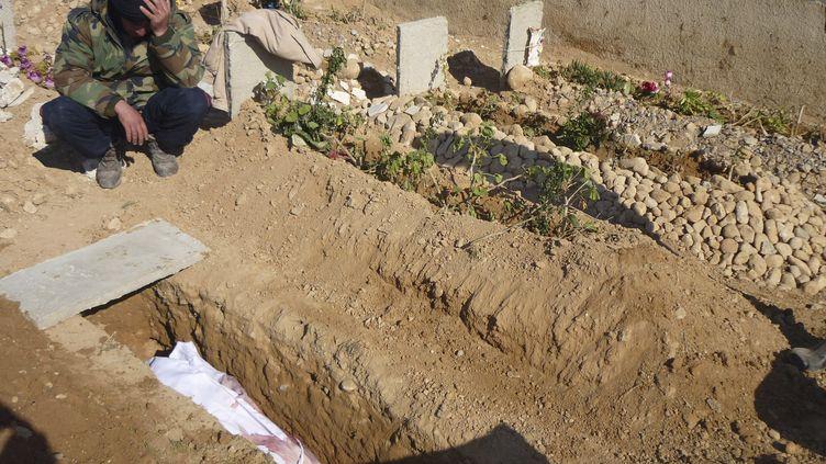 Un soldat de l'Armée syrienne libre se recueille sur la tombe de l'un de ses camarades, le 25 mars 2013 à Qusair (Syrie). (REUTERS)