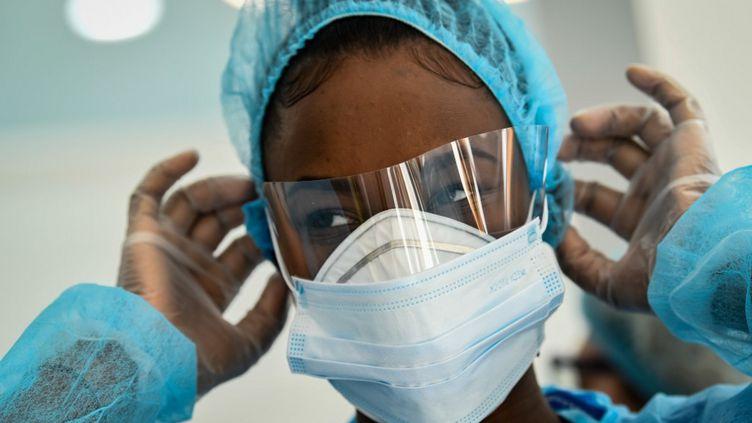 Unefemme ajuste un masque sur sa tenue de protection, à Paris. (BERTRAND GUAY / AFP)