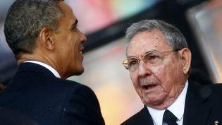 Barack Obama salue le président cubain Raul Castro, le 10 décembre 2013, lors de l'hommage à Nelson Mandela, à Johannesburg (Afrique du Sud). (KAI PFAFFENBACH / REUTERS)