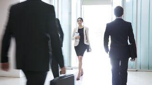 Des hommes et une femme à l'entrée d'une entreprise. Photo d'illustration. (SIGRID OLSSON / MAXPPP)