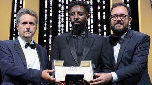 Ladj Ly (au centre) reçoit le Prix du Jury pour Les Misérables, ex-aequo avec les brésiliens Juliano Dormelles et Kleber Mendonça pourBacurau (VALERY HACHE / AFP)