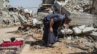 Gaza, quartier de Shejaiya, Palestine, février 2015. Un homme devant les ruines de sa maison. Il a réussi à raccorder l'eau d'un puits avec un tuyau, mais cette eau est impropre à la consommation, comme 96 % de l'eau de l'aquifère côtier qui passe sous Gaza. Surexploité en amont par Israël, celui-ci est infiltré d'eau de mer, mais aussi de pesticides utilisés pour l'agriculture. Durant la guerre, 40 % du réseau d'eau et des infrastructures ont été détruits ou abîmés.  (Laurence Geai / Sipa Press)