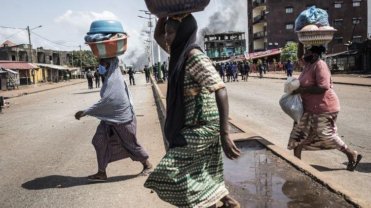 Des femmes traversent la route en courant, dans la capitale guinéenne Conakry, lors d'une manifestation de masse lelendemain dela publication des résultats préliminaires pour cinq communes de la ville, le 21 octobre 2020. (JOHN WESSELS / AFP)